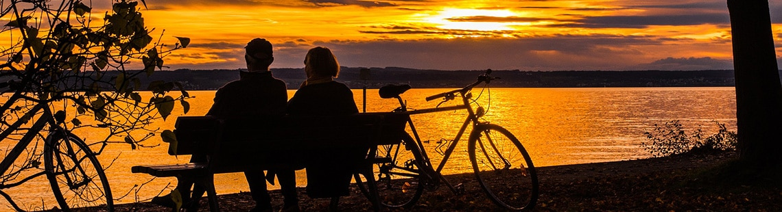 A couple sitting on a bench with bicycles at sunset.